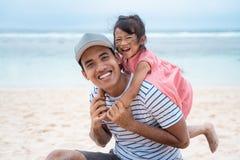 Дочь обнимая его отца от за при игре стоковое фото