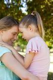 Дочь обнимая ее мать на парке Стоковая Фотография