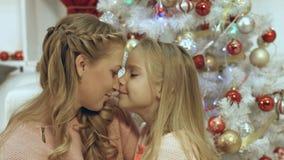 Дочь обнимая и целуя ее мать около рождественской елки Стоковые Фото