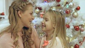Дочь обнимая и целуя ее мать около рождественской елки Стоковая Фотография RF
