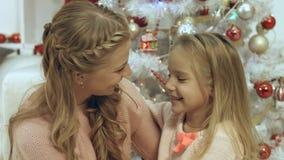 Дочь обнимая и целуя ее мать около рождественской елки Стоковые Изображения