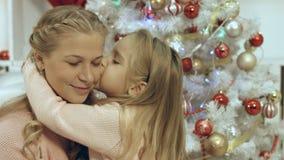 Дочь обнимая и целуя ее мать около рождественской елки Стоковое фото RF
