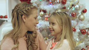 Дочь обнимая и целуя ее мать около рождественской елки Стоковые Фотографии RF