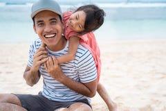 Дочь обнимая с избалованный его отцу от позади стоковое фото rf