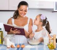 Дочь домохозяйки уча для того чтобы подготовить омлет и усмехаться Стоковое Изображение