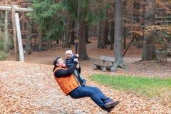 Дочь отца и младенца наслаждаясь ездой zipline стоковое фото rf