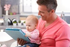 Дочь отца и младенца используя таблетку Стоковое Изображение RF
