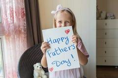 Дочь поздравляет папы и дает ему подарок и открытку Счастливая концепция дня отца стоковое изображение