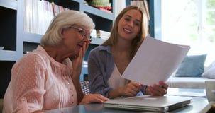 Дочь помогая старшей матери с обработкой документов в домашнем офисе сток-видео