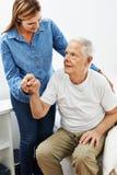 Дочь помогая старшему человеку получая вверх стоковые изображения rf