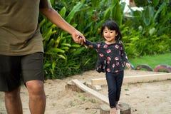 Дочь помогла его отцом с руками удерживания ища баланс стоковые фото