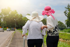 Дочь принимает заботе пожилую женщину идя на улицу стоковое изображение