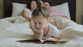 Дочь при семья читая книгу в кровати сток-видео