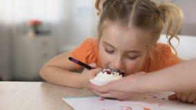 Дочь пробуя сладкий десерт от руки матери, рисуя карандашем на таблице видеоматериал