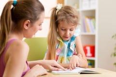 Дочь ребенка матери уча к читать Стоковые Изображения