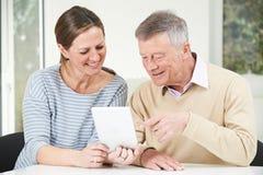 Дочь старшего человека и взрослого смотря таблетку цифров совместно стоковое фото