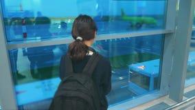 Дочь с концепцией аэропорта полетов самолета рюкзака Подросток девушки со смартфоном смотрит вне окно на акции видеоматериалы