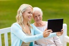 Дочь с ПК таблетки и старшей матерью на парке стоковое фото rf
