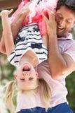 Дочь удерживания отца вверх ногами Outdoors стоковое фото rf