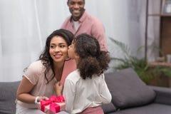 Дочь целуя мать и представляя подарки к ей на день матерей стоковые фотографии rf