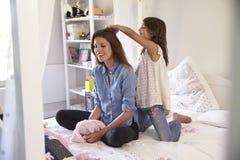 Дочь чистит волосы щеткой ` s матери по мере того как они сидят в спальне ` s девушки Стоковая Фотография RF