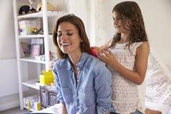 Дочь чистит волосы щеткой ` s матери по мере того как они сидят в спальне ` s девушки Стоковые Фото
