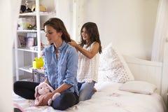 Дочь чистит волосы щеткой ` s матери по мере того как они сидят в спальне ` s девушки Стоковое Изображение RF
