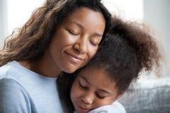 Дочь preschool любящего черного объятия матери маленькая стоковые изображения