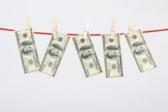 Долларовые банкноты американца 100 денег вися на прачечной выравниваются Стоковое Изображение RF