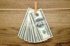 Долларовые банкноты вися на штыри одежд Стоковые Изображения RF