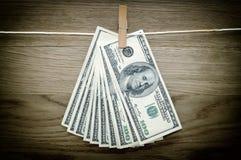 Долларовые банкноты вися на штыри одежд Стоковые Фото