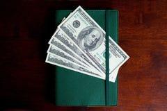 Доллары банкнот в тетради Стоковое фото RF
