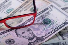 Доллары банкнот и стекел Стоковая Фотография