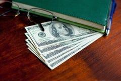 Доллары банкнот, тетради, стекел, ручки Стоковая Фотография RF