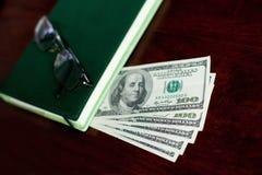 Доллары банкнот, тетради, стекел Стоковая Фотография RF