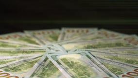 Доллары вращаются против черной предпосылки На заднем плане световые лучи акции видеоматериалы
