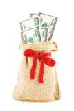 Доллары в linen мешке, перевязанном лентой красного цвета подарка стоковое изображение rf
