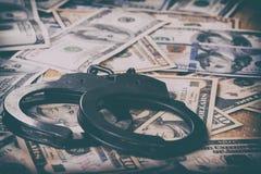 Доллары и наручники Финансовое злодеяние, незаконная деятельность стоковая фотография