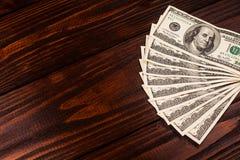 Доллары на деревянном столе Стоковая Фотография