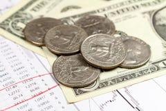 Доллары США банкнот с монетками на предпосылке план-графика роста валюты Фокус на переднем плане Стоковая Фотография