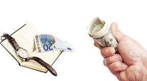 Доллары США в руке и блокноте с евро и наручными часами Стоковое Фото