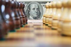 Доллары США и шахмат вычисляют на старое chessboar Стоковое Изображение RF