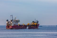 Драгируя корабль в гавани стоковое изображение