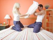 драка пар кровати имея детенышей подушки kneeling стоковая фотография