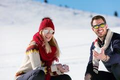Драка Snowball Пары зимы имея потеху сыграть в снежке outdoors Молодые радостные счастливые мульти-расовые пары стоковые изображения