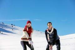 Драка Snowball Пары зимы имея потеху сыграть в снежке outdoors Молодые радостные счастливые мульти-расовые пары стоковые фотографии rf