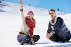 Драка Snowball Пары зимы имея потеху сыграть в снежке outdoors Молодые радостные счастливые мульти-расовые пары стоковая фотография