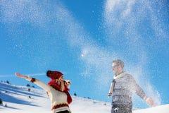 Драка Snowball Пары зимы имея потеху сыграть в снежке outdoors Молодые радостные счастливые мульти-расовые пары стоковое фото rf