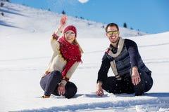 Драка Snowball Пары зимы имея потеху сыграть в снежке outdoors Молодые радостные счастливые мульти-расовые пары стоковое изображение
