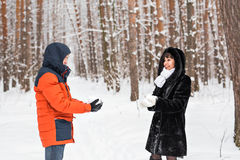 Драка Snowball Пары зимы имея потеху сыграть в снежке outdoors стоковое фото rf
